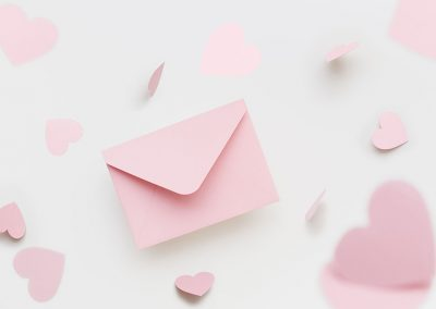Flying pink envelope surrounded with flying pink hearts on the white background. Valentines Day greeting concept